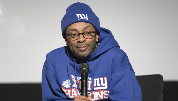 Spike Lee sits in front of a projection screen in a blue New York Knicks sweatshirt and matching knit cap