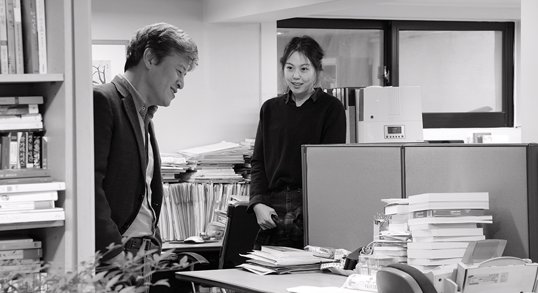 a black and white image of a standing man and woman talking in an office