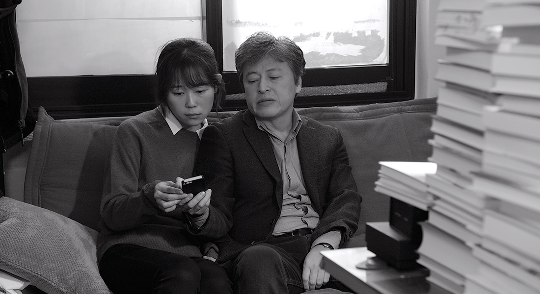 a black an dwhite image of a man and a woman looking down on a phone