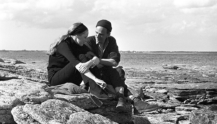 A black and white photo of a white man and a white woman sitting on a cliff by the sea.