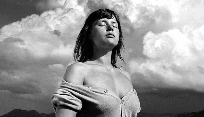 a black and white image in a sweater pulled down below her shoulders with eyes closed against a cloudy sky
