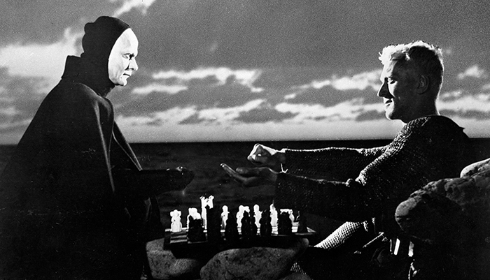 A black and white image of a man in a mask standing across from another man.