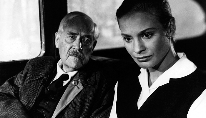Black and white photo of an older male actor and younger female actress sitting in a car.