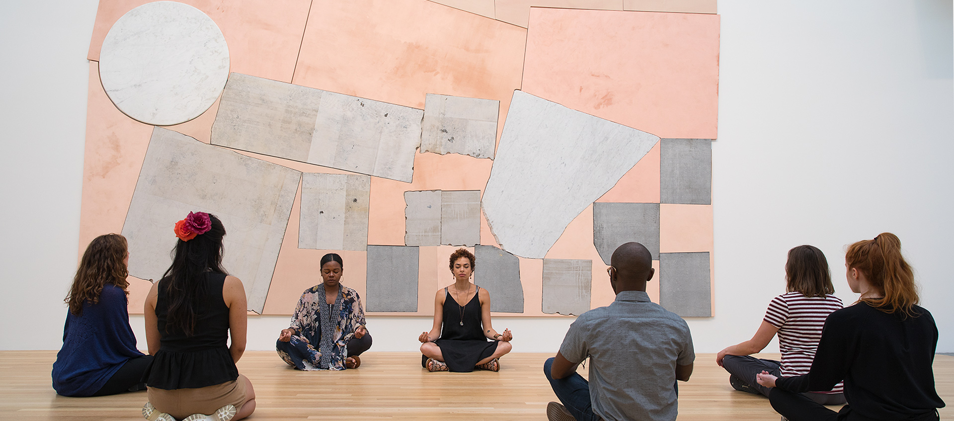 a group of people practicing yoga with an art work installation behind them