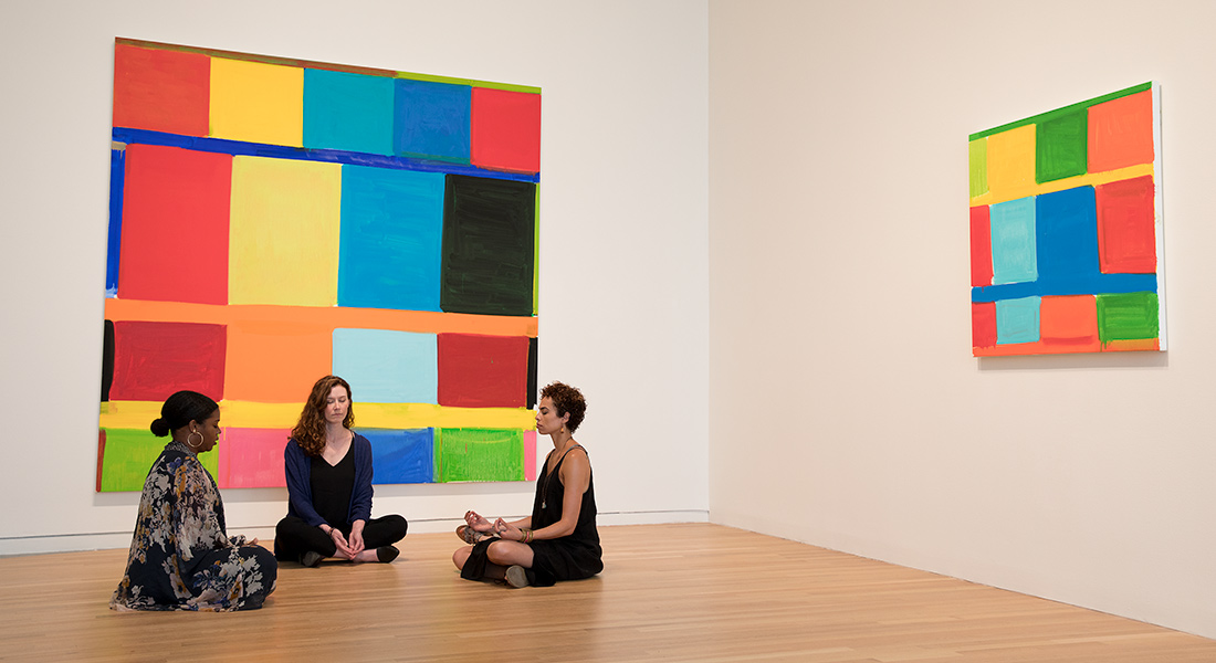 three women in a yoga pose in front of two colorful art installations