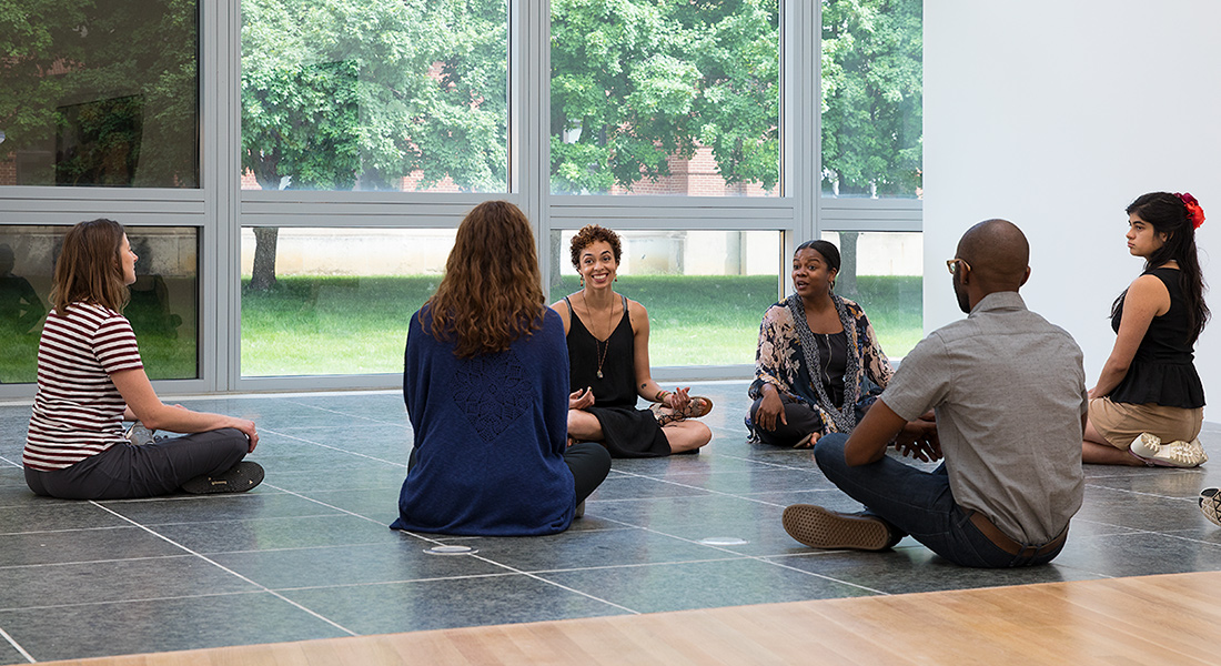 six people seated in yoga poses in the Wexncer Center gallery space