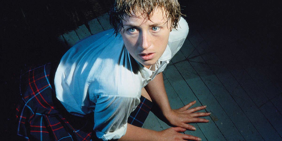 Color portrait of Cindy Sherman with hands on the floor, looking up and to the left