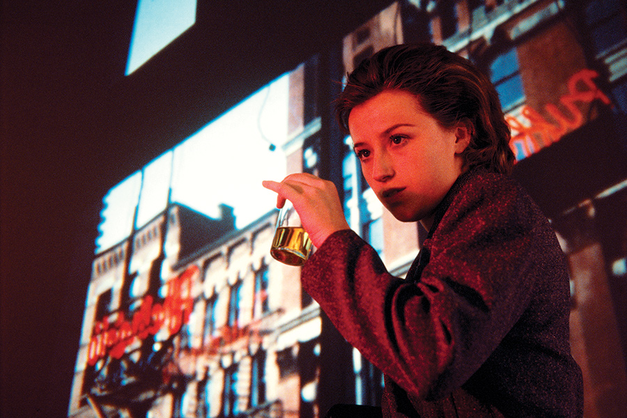 Color portrait of Cindy Sherman holding a drink against a rear screen projection