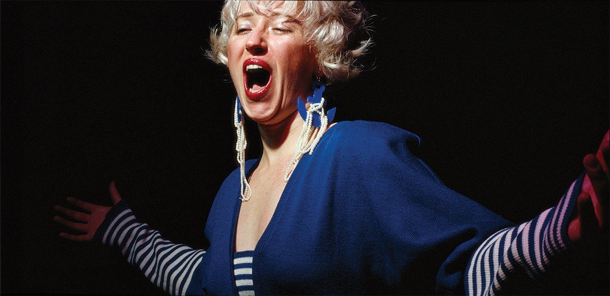Color portrait of Cindy Sherman singing with arms outstretched