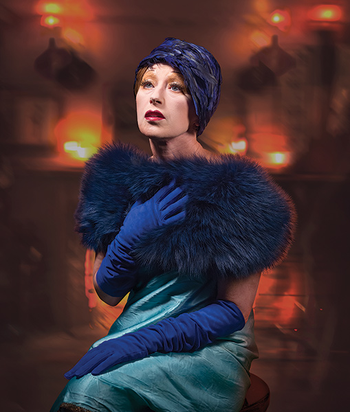 Color portrait of Cindy Sherman wearing blue gloves and a teal dress