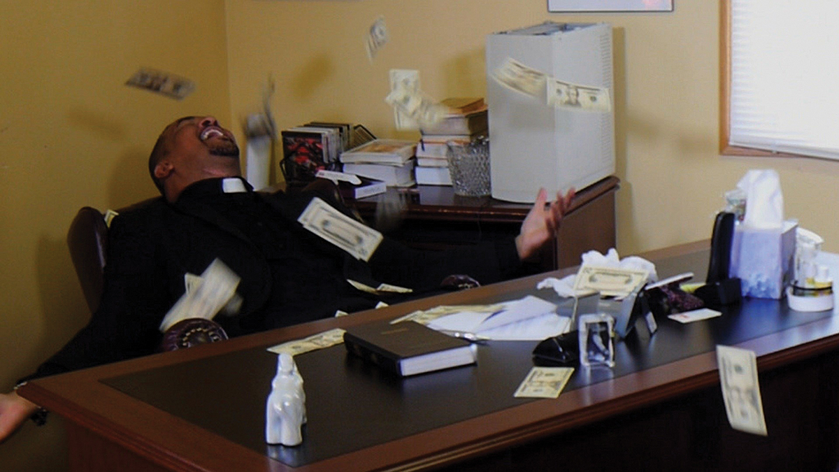 Film still of a priest sitting at a desk throwing dollar bills into the air