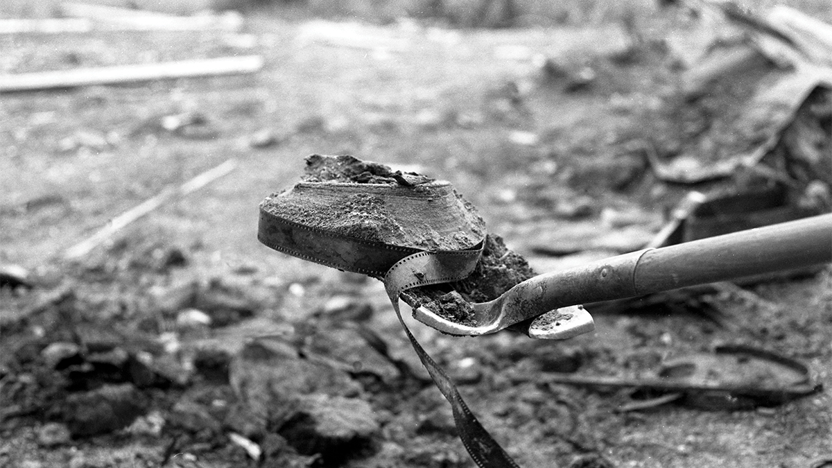 Film still of a shovel lifting a burnt film reel