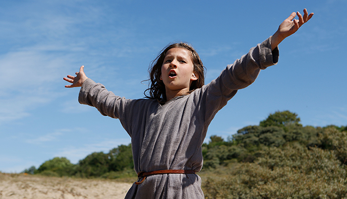 Promotional still image of a young woman singing with arms outstretched, from the 2018 Bruno Dumont film Jeannette: The Early Childhood of Joan of Arc