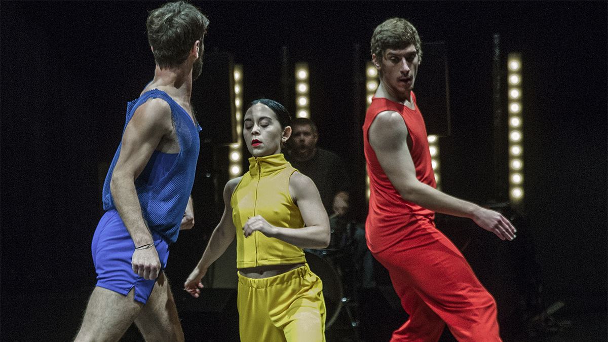 three dancers on stage wearing red, blue, and yellow