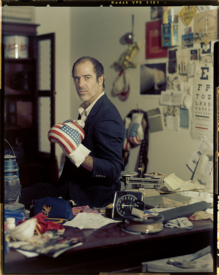 Old photo of Artist sitting on desk with an American Flag-patterned boxing glove