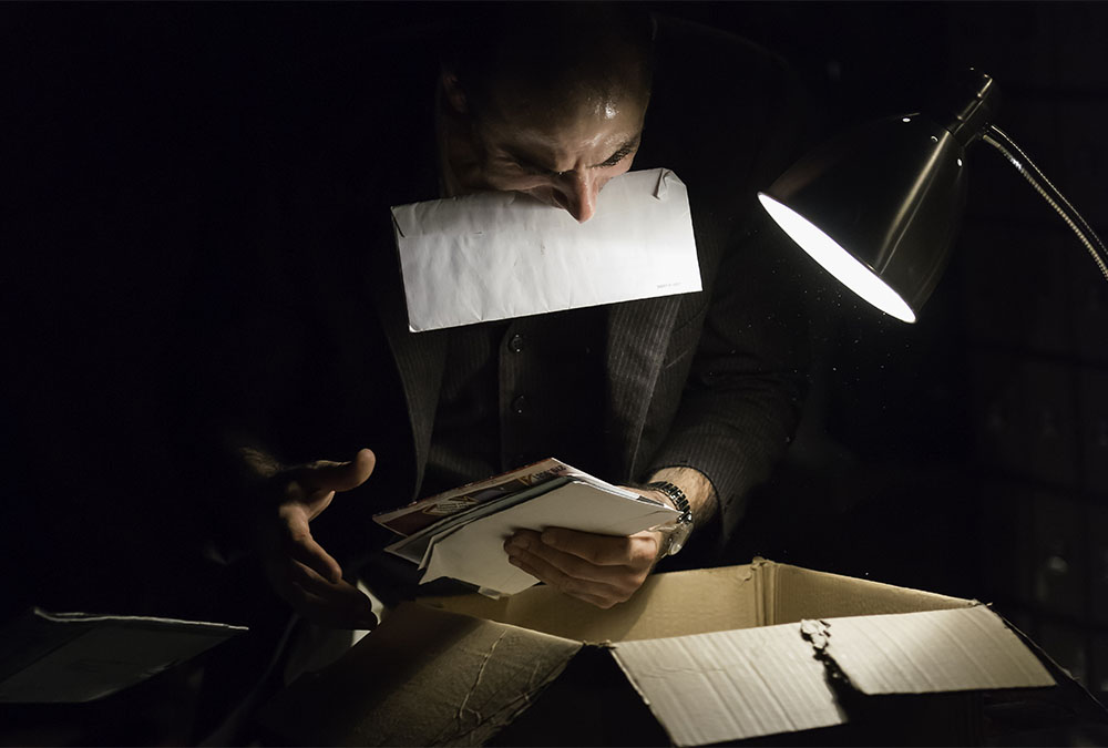 Artist searching through a box with paper in his mouth