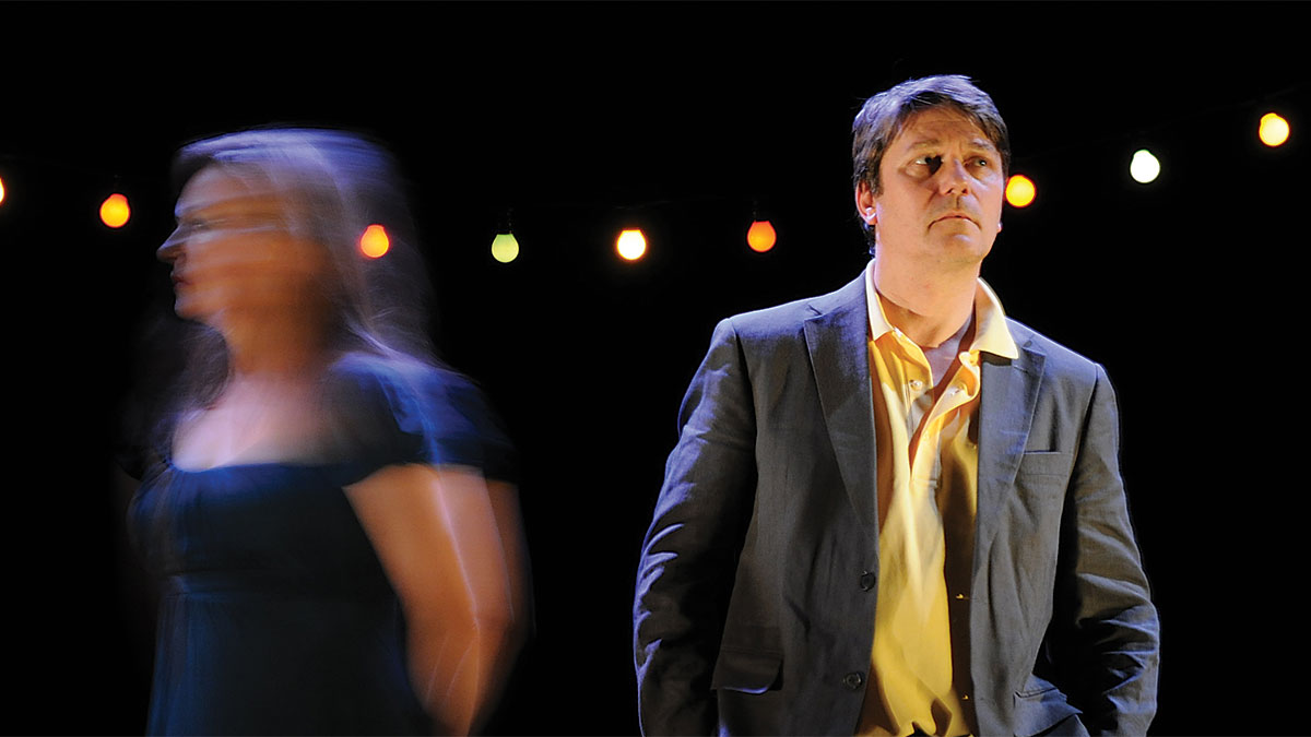 Women in black dress and man in yellow shirt standing side by side with a blur
