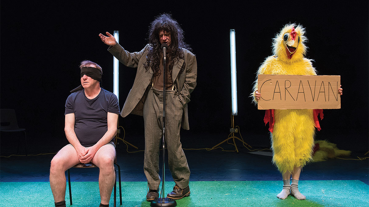 "Performers on stage: A blindfolded man listens while another sings next to a performer in a chicken costume holding a sign that reads ""caravan"""