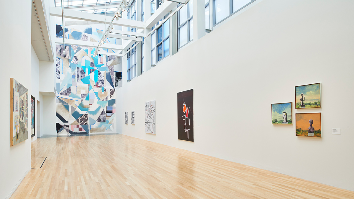 Installation view of showing multiple works and a large mural in the Wexner Center galleries.