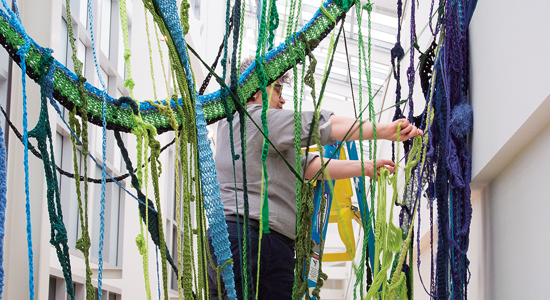 Artist Sheila Pepe installing large strands of yarn to the walls of the Wexner Center galleries