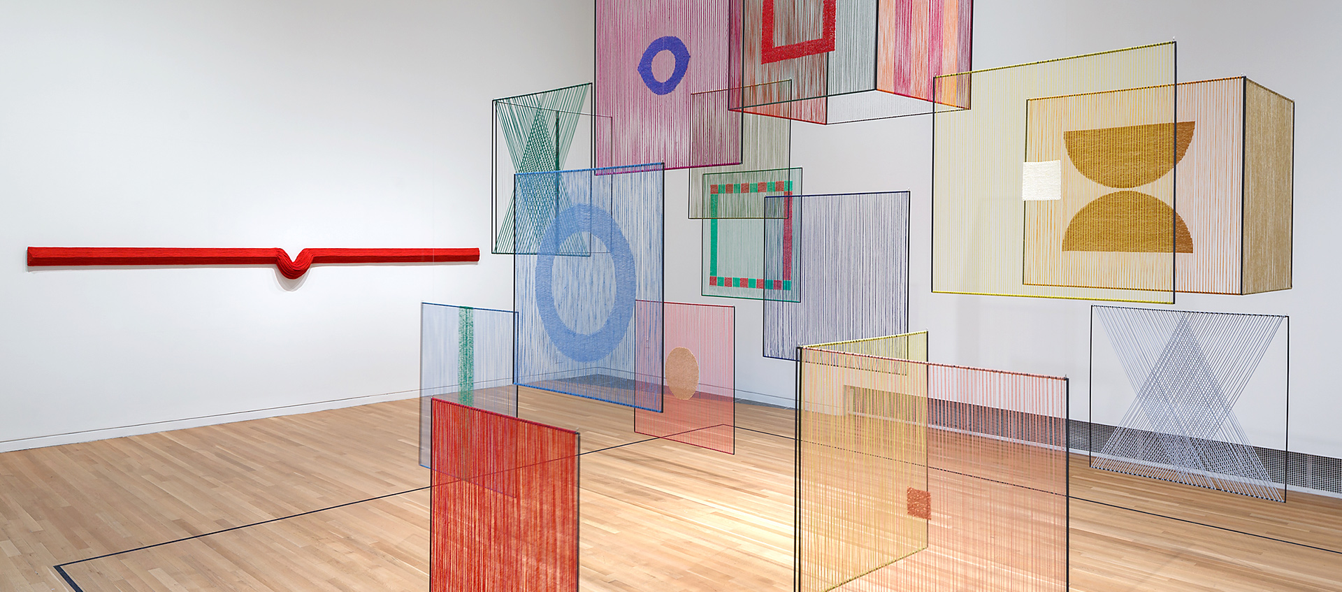 Large geometric textile shapes of different colors hanging from the ceiling the Wexner Center galleries