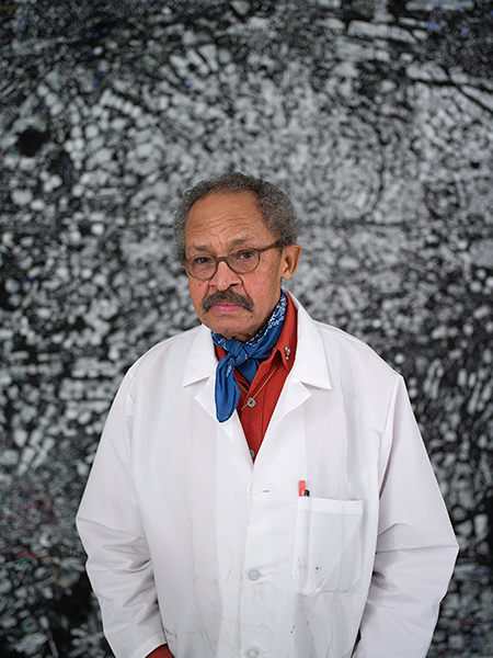 Portrait of Jack Whitten standing in front of one of his works
