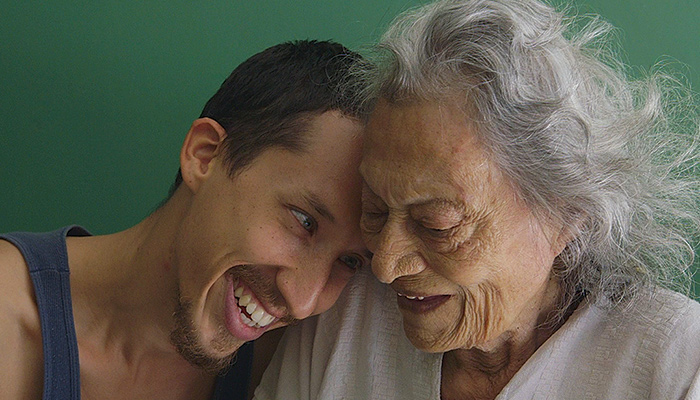 Diego Alvarez-Serrano and his grandmother América sit and cuddle together in a scene from Erick Stoll and Chase Whiteside's 2018 documentary América
