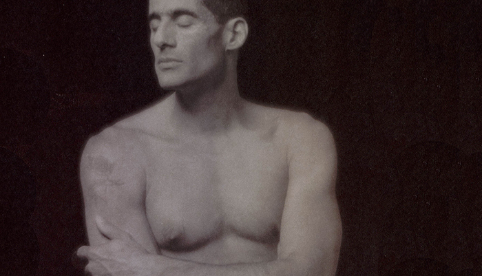 A shirtless man with his eyes closed.