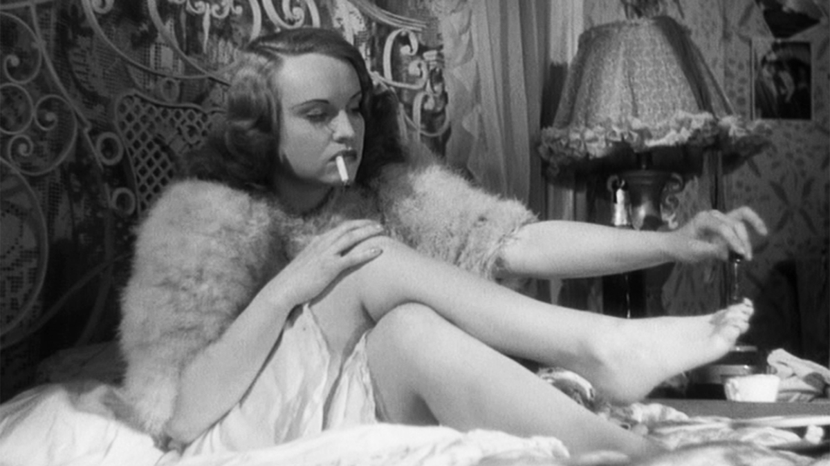 A woman in bed painting her toenails with a cigarette in her mouth