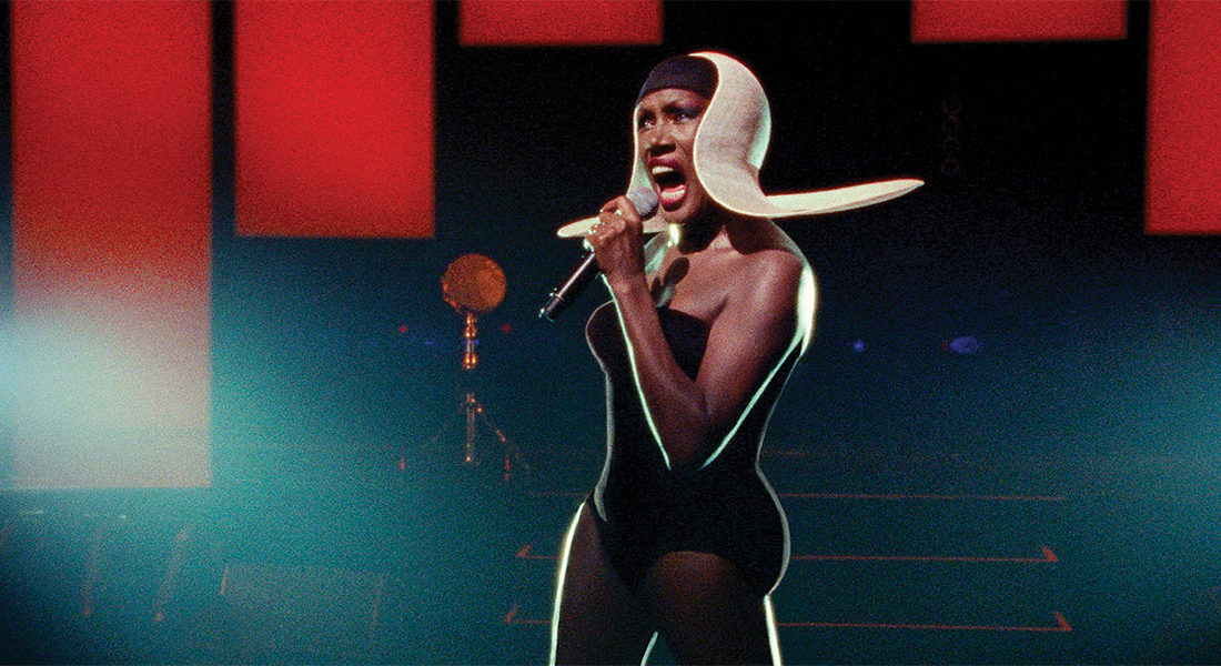 a film still of Grace Jones singing into a mic