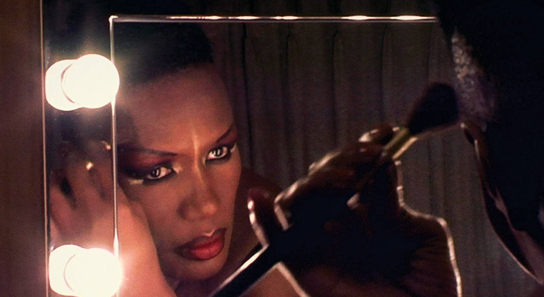 a film still of Grace Jones applying make up in front of a mirror