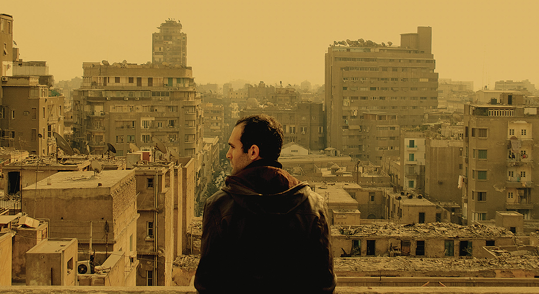 A man seen from behind, looking across a yellow-tinted cityscape