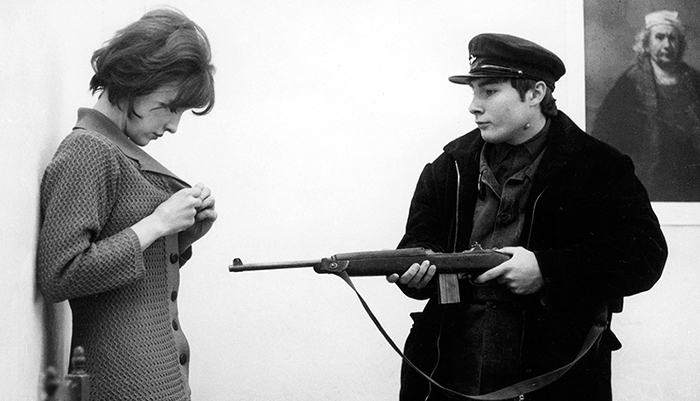 A man holds a rifle at a women in a black and white movie still