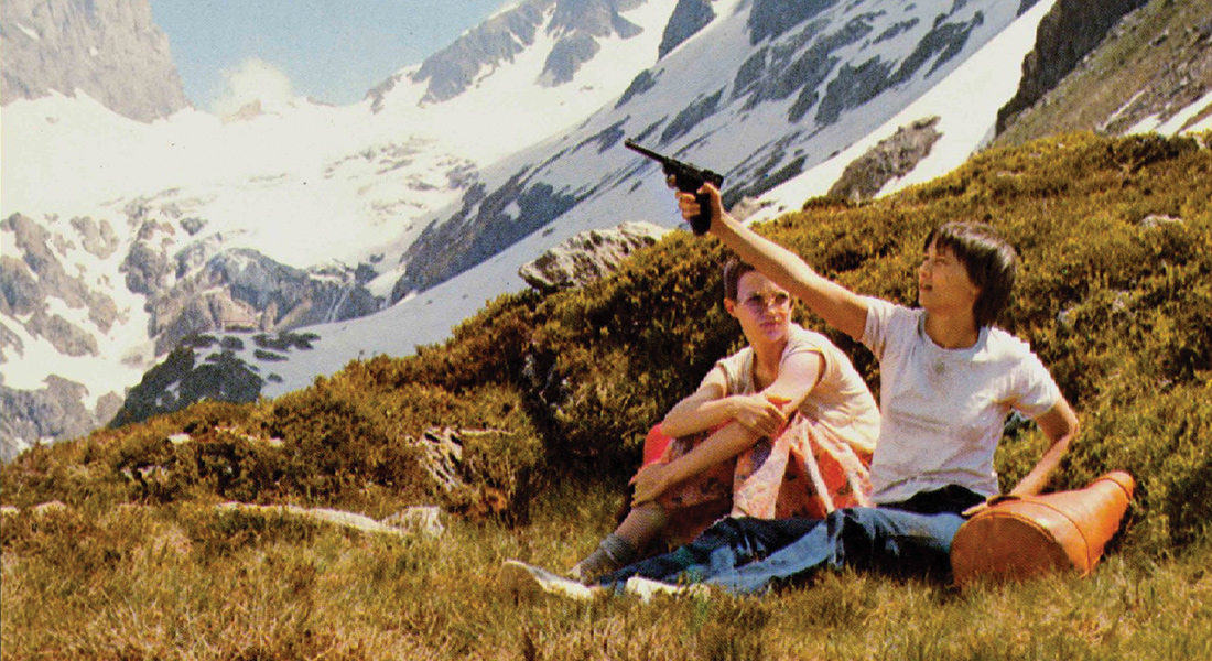 Two woman sit on mountainside, one holds a gun