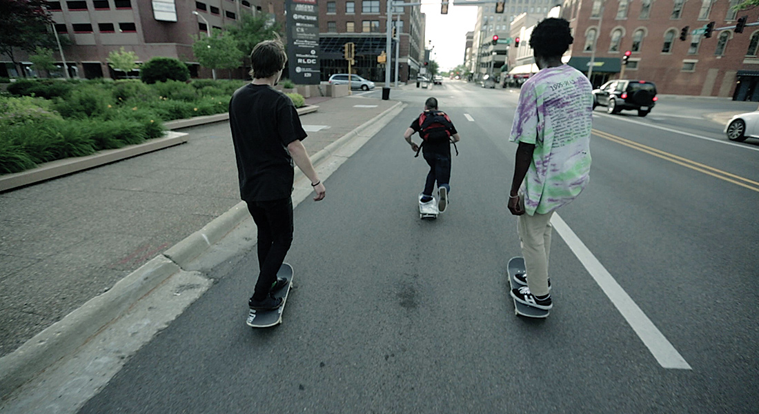 Three boys skate on the road