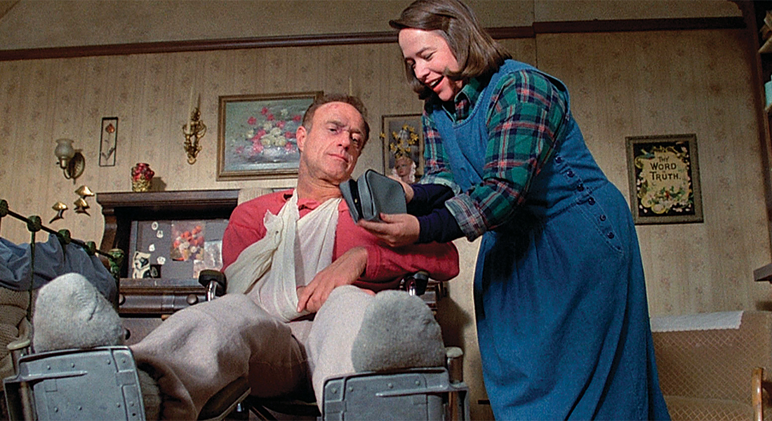 film still of Kathy Bates as Annie Wilkes and James Caan as Paul Sheldon in a wheelchair