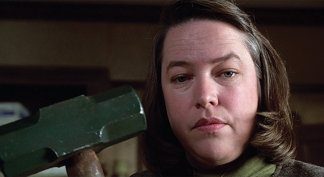 film still of Kathy Bates as Annie Wilkes with a hammer in hand