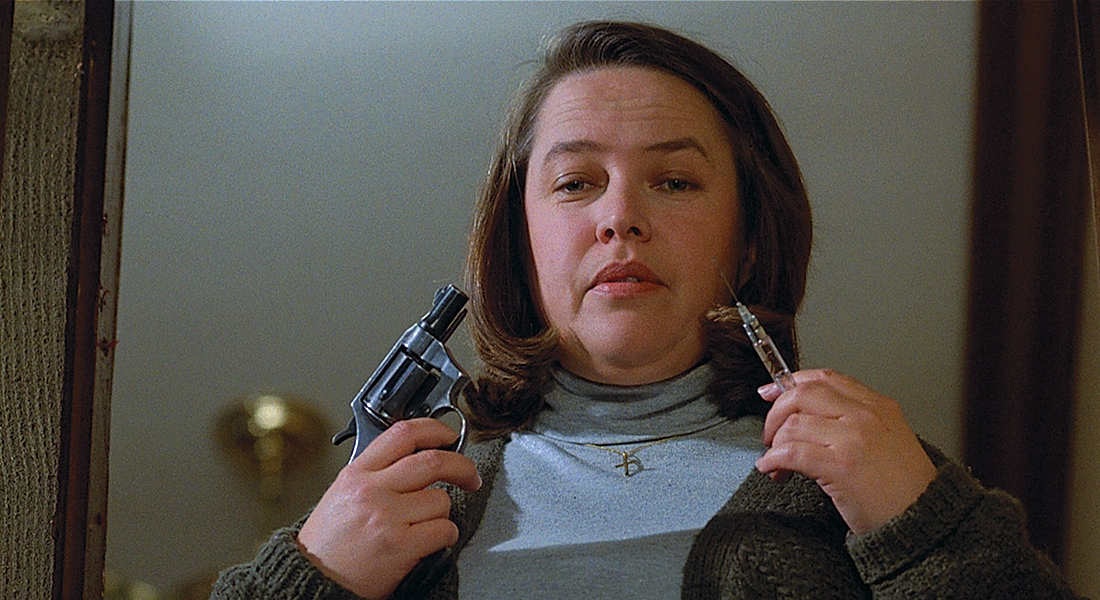 film still of Kathy Bates as Annie Wilkes with a gun in one hand and a syringe in another
