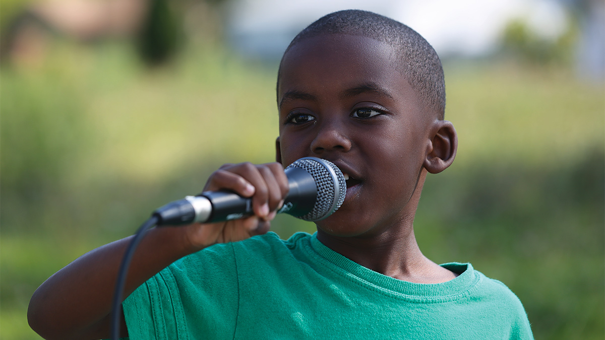 Film still of a young boy speaking into a microphone.