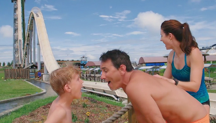 (right to left) son, father, and mother in front of a waterslide