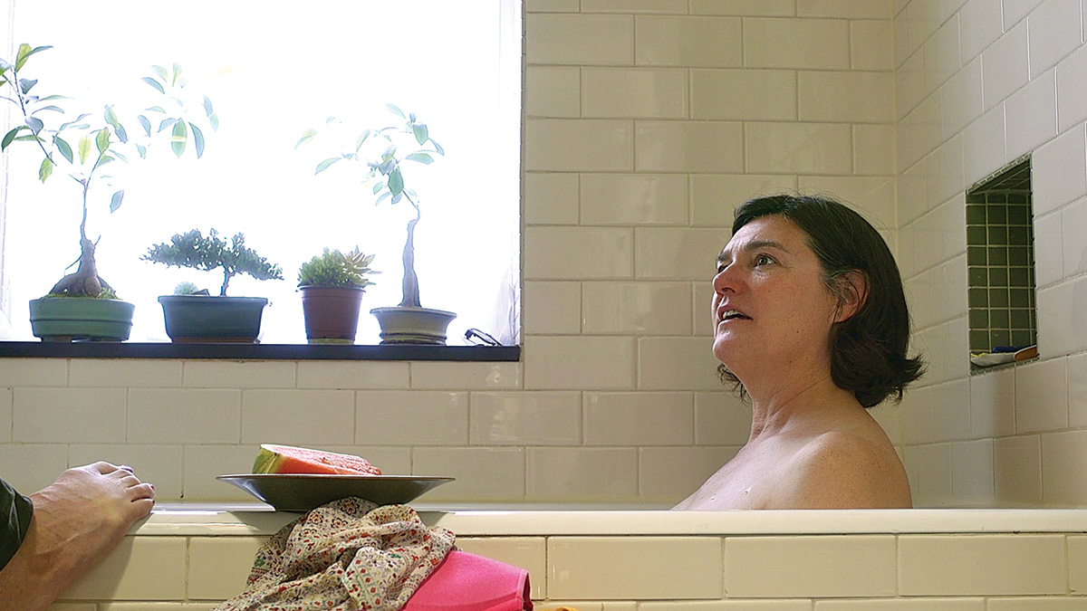 Film still of a woman in a tub looking at someone off-camera.