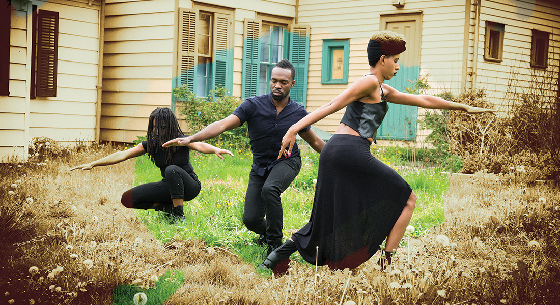 Three people dance in an outdoor space