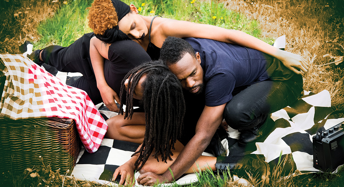 Three people lean on one another on a checkered blanket outside