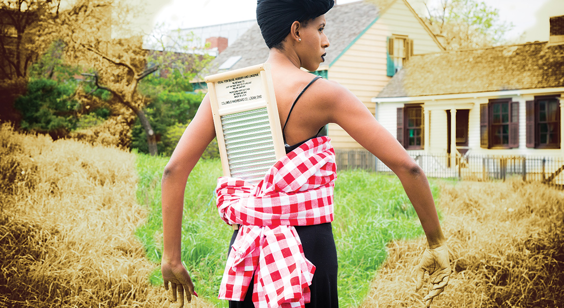 A woman stands outdoors, a checkered cloth holds a washboard on her back