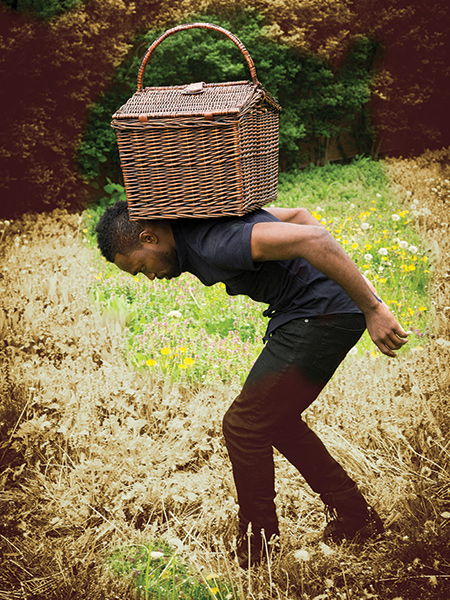 A man stands hunched over, a basket on his back