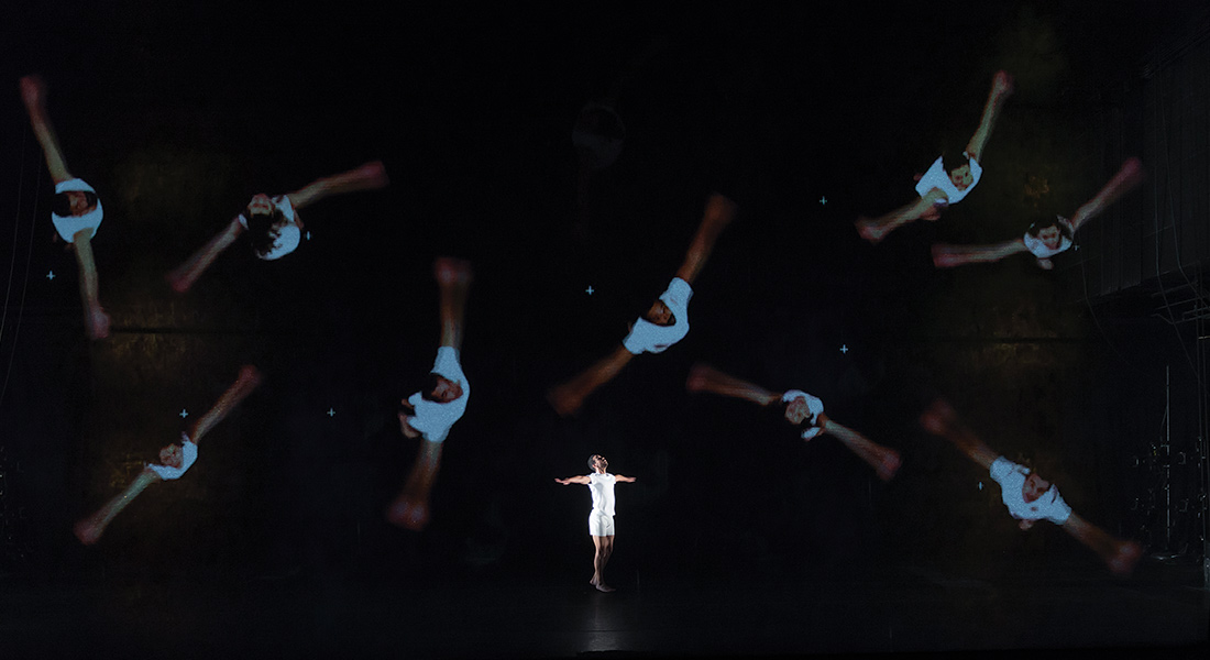 Single dancer at center stage with projected images behind