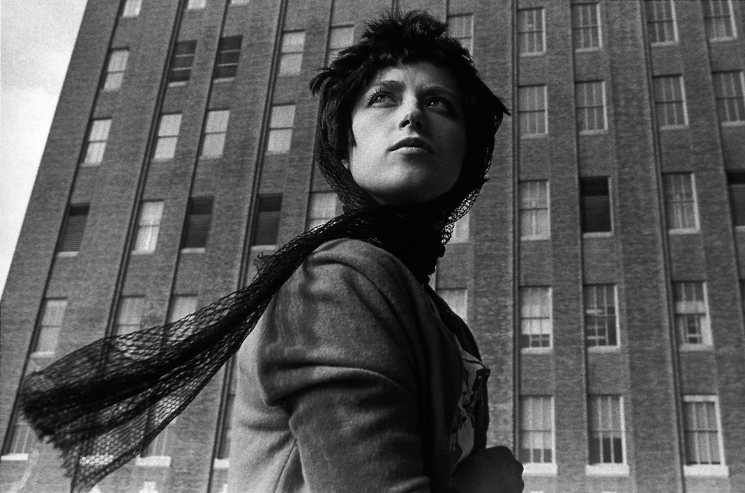 cindy sherman with a head scarf in front of a multilevel story building