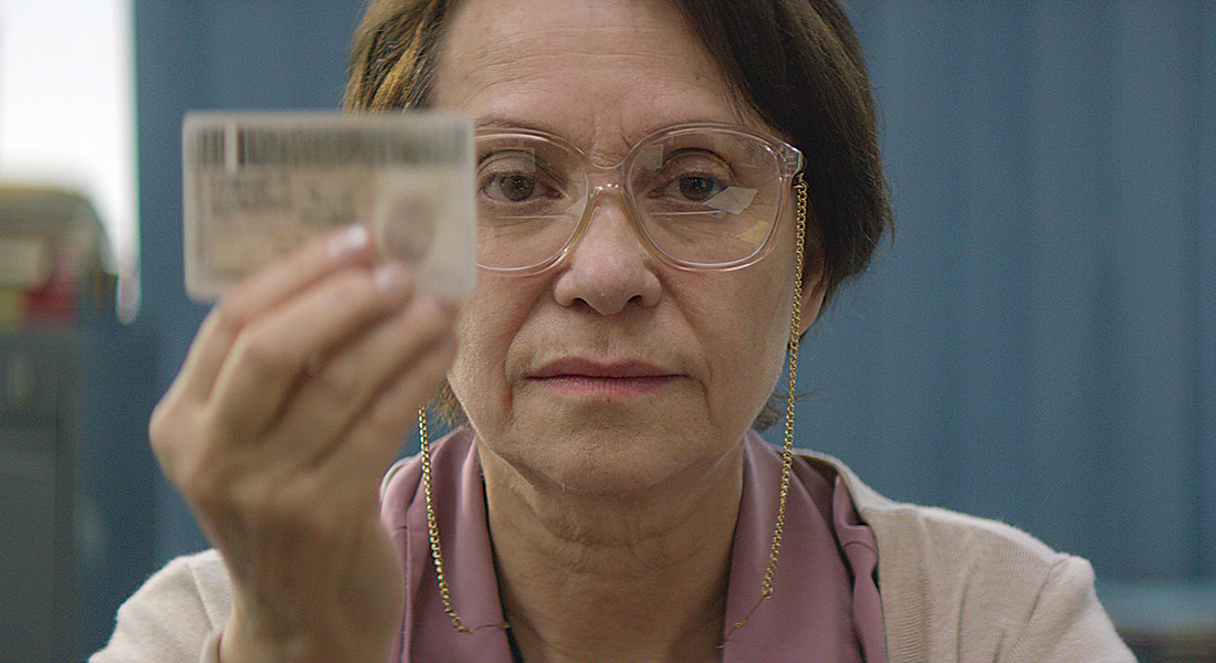 A middle-aged Latino woman in glasses seen in close up against a blue wall, facing the camera and holding an ID card up in front of her