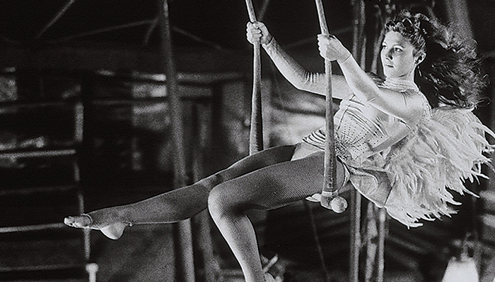 Actress Solveig Dommartin swings on a trapeze in an angel costume in a still from the 1987 Wim Wenders film Wings of Desire
