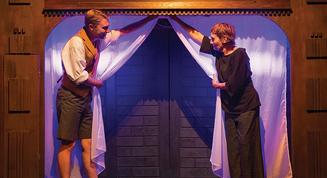 Two people pull back the curtains to a small stage door